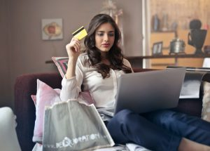 woman sitting with a computer on her legs holding a credit card